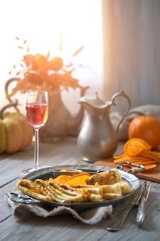 Crepes suzette na placa de metal vintage na mesa de madeira servida com molho de laranja