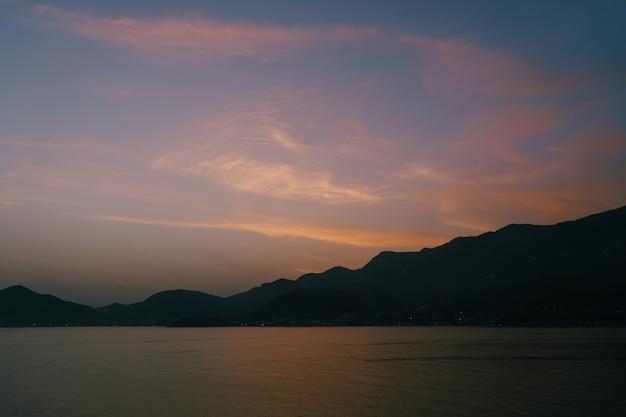 Crepúsculo após o pôr do sol sobre as montanhas e o mar