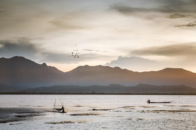 Crepúsculo da cena do por do sol no lago com céu azul e clounds no lago kwan do payao na província do phayao, tailândia.