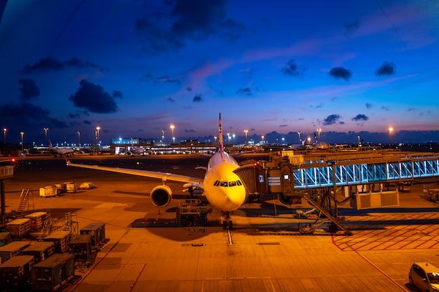 Crepúsculo da noite no aeroporto com um avião
