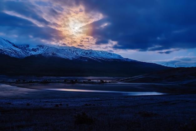 Crepúsculo do amanhecer sobre o lago dzhangyskol no trato yeshtykol e o cume chuysky do norte ao luar. rússia, república altai