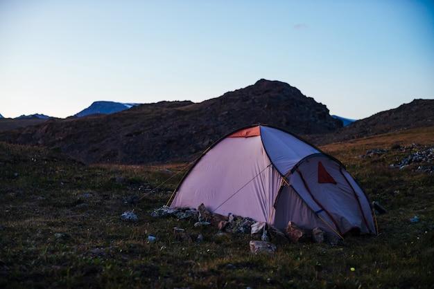 Crepúsculo nas montanhas com tenda na passagem na luz violeta.