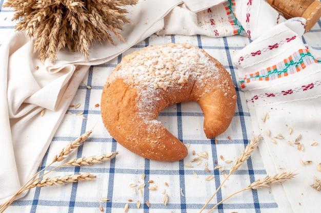 Crescente bagel polvilhado com açúcar de confeiteiro. em uma toalha de mesa listrada de azul branco. perto de grãos e espigas de milho. vista de cima. estilo sertanejo.