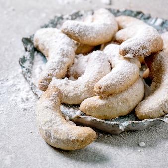 Crescentes de baunilha de biscoitos caseiros tradicionais de natal com açúcar de confeiteiro. na placa de cerâmica sobre fundo cinza claro. fechar-se