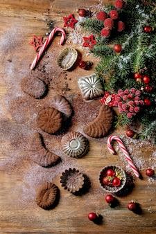 Crescentes de chocolate caseiros tradicionais de biscoitos de casca de árvore de natal com açúcar de confeiteiro de cacau em placa de cerâmica com moldes de biscoitos, árvore do abeto, decorações de estrelas de natal vermelhas sobre a superfície de madeira. postura plana