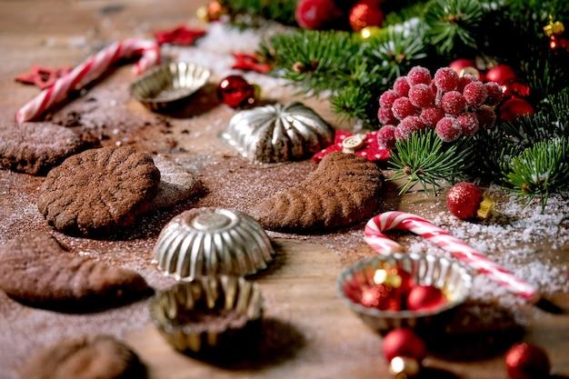 Crescentes de chocolate caseiros tradicionais de biscoitos de casca de árvore de natal com açúcar de confeiteiro de cacau em placa de cerâmica com moldes de biscoitos, árvore do abeto, decorações de estrelas de natal vermelhas sobre a superfície de madeira.