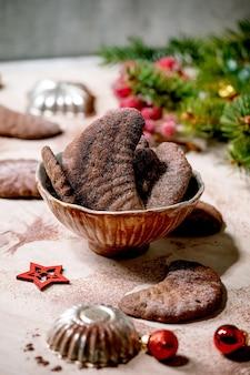 Crescentes de chocolate caseiros tradicionais de biscoitos de casca de árvore de natal com açúcar de confeiteiro de cacau em placa de cerâmica com moldes de biscoitos, árvore do abeto, decorações de estrelas de natal vermelhas. superfície de mármore rosa.