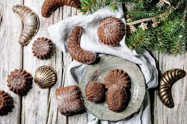 Crescentes de chocolate caseiros tradicionais de biscoitos de casca rija de natal com açúcar de confeiteiro de cacau em placa de cerâmica com moldes de biscoitos, árvore do abeto, decorações de estrelas de natal sobre a superfície de madeira. postura plana