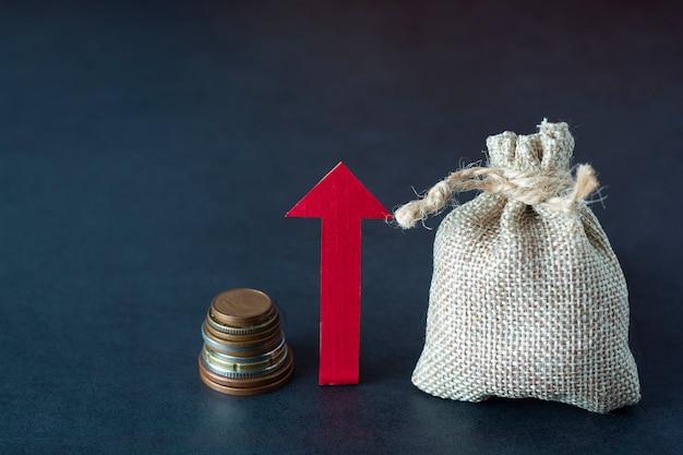 Crescer, aumentar ou aumentar sua renda com flecha direcional, dinheiro e uma bolsa no escuro. financeiro. copyspace.