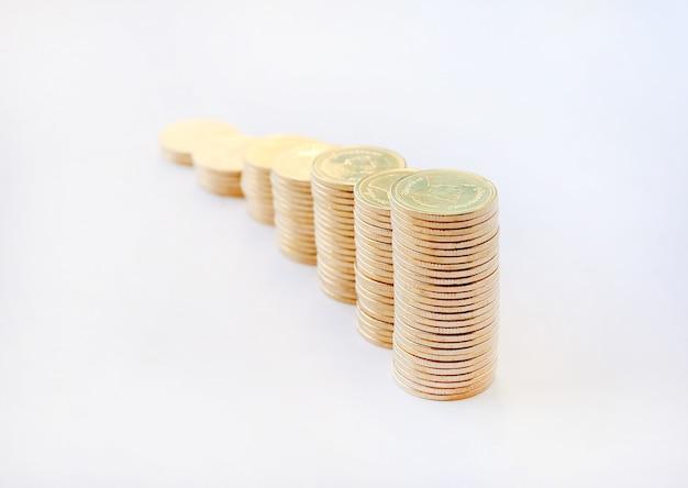 Crescimento da pilha das moedas de ouro no fundo, na finança do negócio e no conceito brancos do dinheiro.