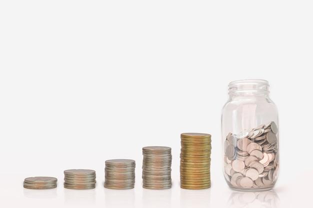 Crescimento da pilha e do dinheiro da moeda na garrafa de vidro, no fundo branco. investimento do conceito de poupar dinheiro.