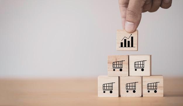 Crescimento da venda de negócios e expansão do conceito de franquia de loja, cubo de madeira colocando à mão