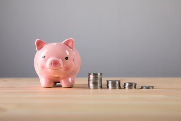 Crescimento de moedas e um cofrinho na mesa