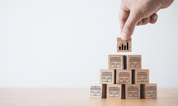 Crescimento de venda de negócios e expansão de conceito de franquia de loja, mão colocando bloco de cubo de madeira que loja de tela de impressão e supermercado.