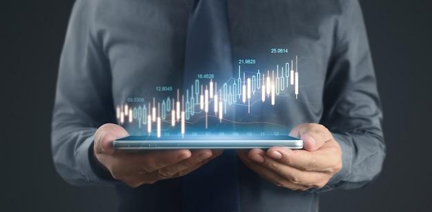 Crescimento do gráfico do plano de empresário e aumento dos indicadores positivos do gráfico em um tablet na mão