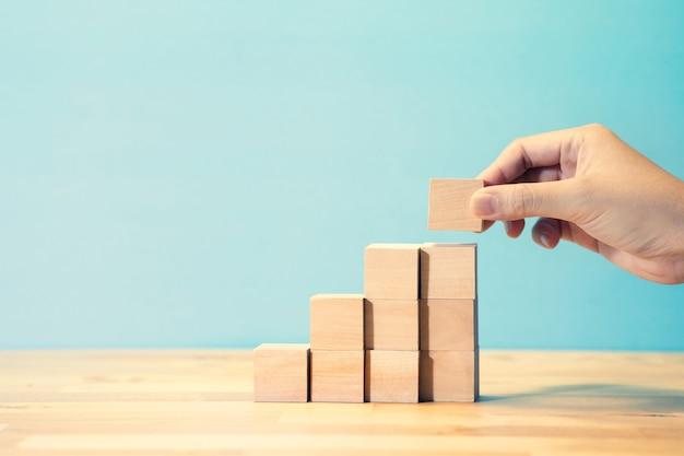 Crescimento do negócio ou etapa para conceitos de sucesso com a mão da pessoa colocando a etapa do blog de madeira