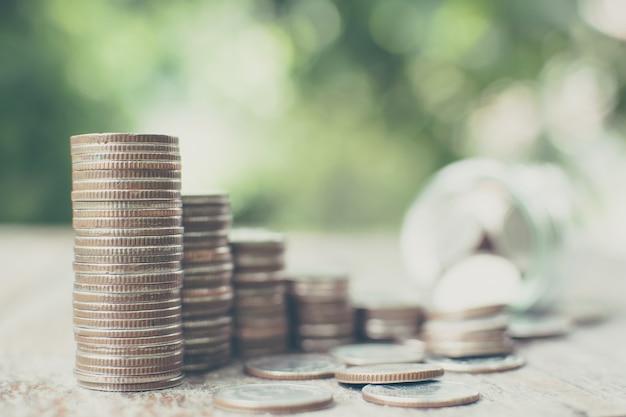 Crescimento do passo da pilha de moedas de dinheiro com jar de fundo borrado e folha verde