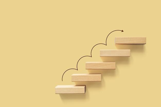 Crescimento ou aumento do conceito de design. escada de bloco em cubo movendo-se passo crescendo até o alvo. realização de sucesso ou motivação de negócios por objetivo
