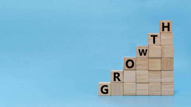 Crescimento. palavra crescimento escrita na pilha de blocos de cubos de madeira sobre fundo azul, crescimento dos ganhos, tendência de mercado, ideia, finanças, estratégia, início de negócios, marketing online, objetivo e conceito de plano de destino