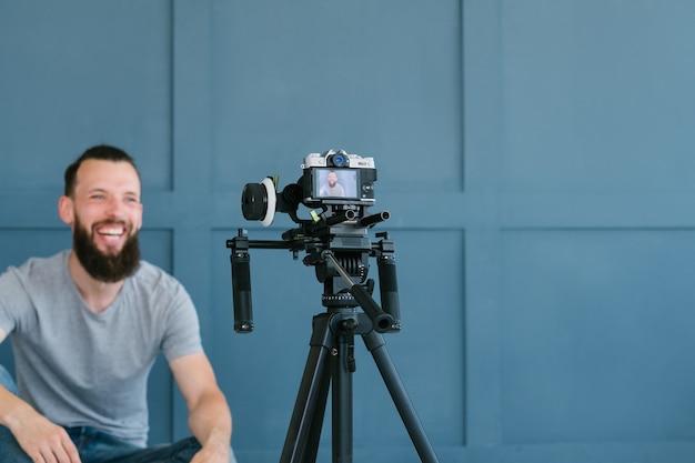 Criação de conteúdo para mídias sociais. blogger gravando um vídeo de si mesmo usando a câmera no tripé. homem barbudo hippie sorridente