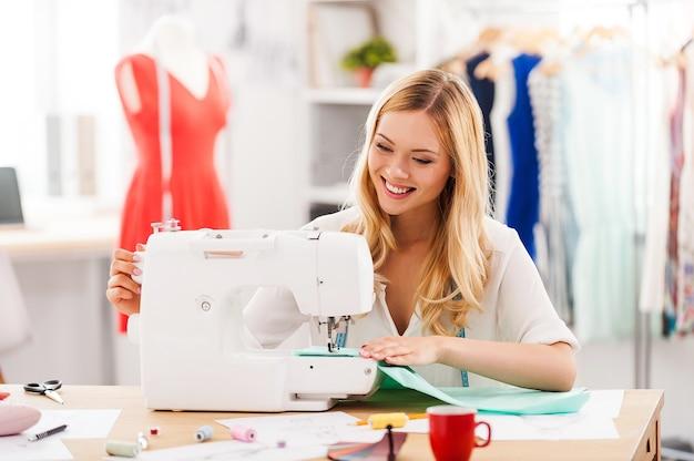 Criação de novos estilos de moda. jovem alegre costurando enquanto está sentada em seu local de trabalho na oficina de moda