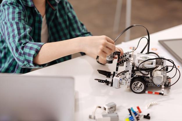 Criação de robôs cibernéticos. rapaz inteligente capaz sentado na escola e usando dispositivos digitais enquanto estuda e expressa alegria
