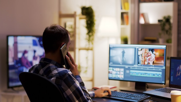 Criador de conteúdo falando ao telefone enquanto trabalha em um projeto multimídia usando software moderno para pós-produção.