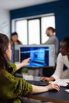 Criador de jogadores explicando ao trabalhador africano como testar a interface de nível de jogo e desenvolver um novo design em um escritório criativo apontando para a tela