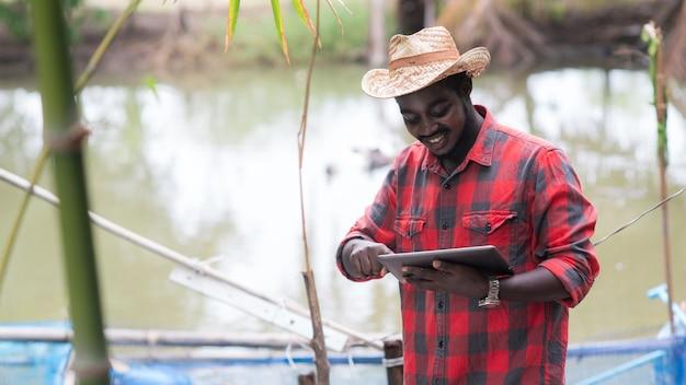 Criador de peixes africano trabalhando com tabket na fazenda de inovação. conceito de agricultura ou cultivo