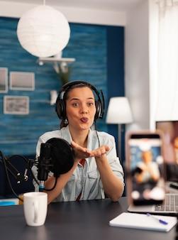 Criador do blogger dando beijos de sopro enquanto grava podcast de talk show. influenciador de mídia social criando conteúdo profissional com equipamentos modernos e estação de streaming digital de internet na web