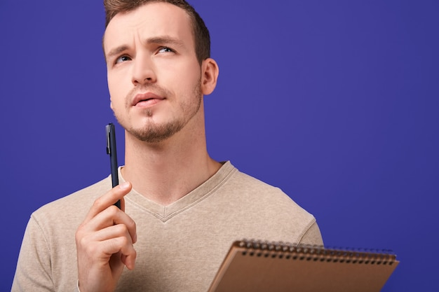 Criador pensativo com caderno de papel e caneta esferográfica, olhando para cima