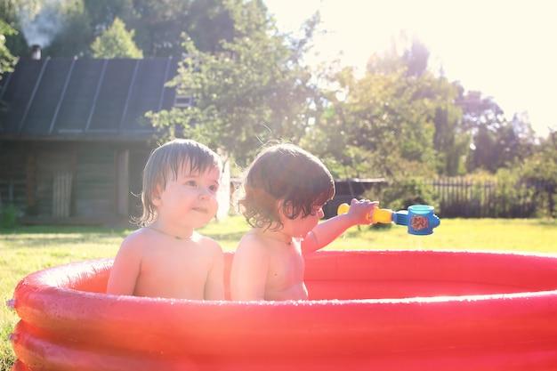 Criança a espirrar na banheira ao ar livre