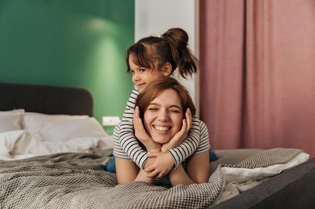 Criança abraça a mãe. mulher e filha deita-se na cama.