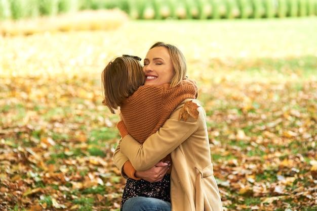 Criança abraçando a mamãe na floresta de outono