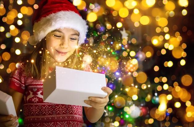 Criança abre presentes debaixo da árvore de natal. foco seletivo.