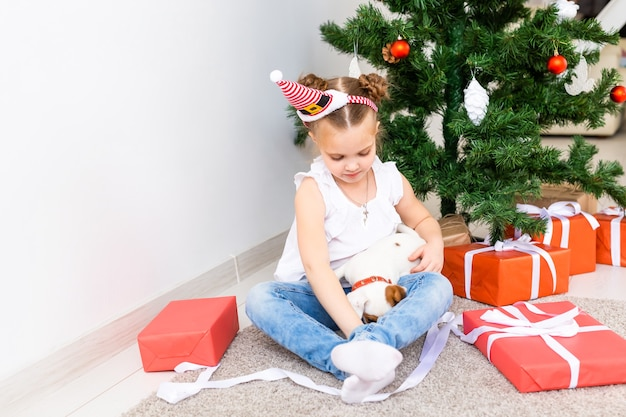 Criança abrindo presentes de natal. criança debaixo da árvore de natal com caixas de presente.