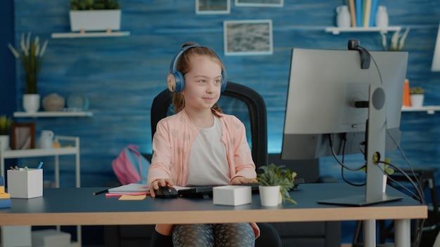 Criança acenando para a câmera da videochamada enquanto usa fones de ouvido