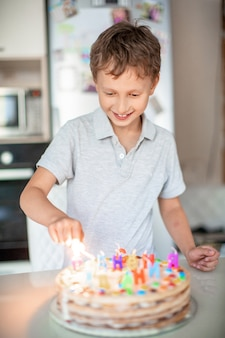 Criança acende velas em um bolo de aniversário. festa de aniversário em casa. europeu