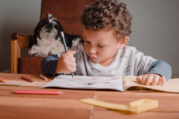 Criança acompanhada por seu animal de estimação ao fazer tarefas de desenho escolar. estudo em casa