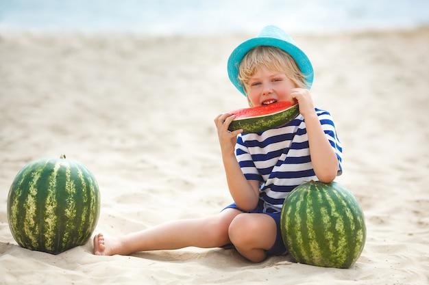 Criança adorável à beira-mar, comendo melancia suculenta. criança alegre no horário de verão na praia. menino bonitinho ao ar livre