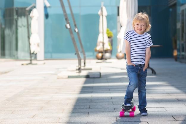 Criança adorável ao ar livre. criança bonita alegre bonita segurando o skate menino casual nas horas de verão patinando em um skate.