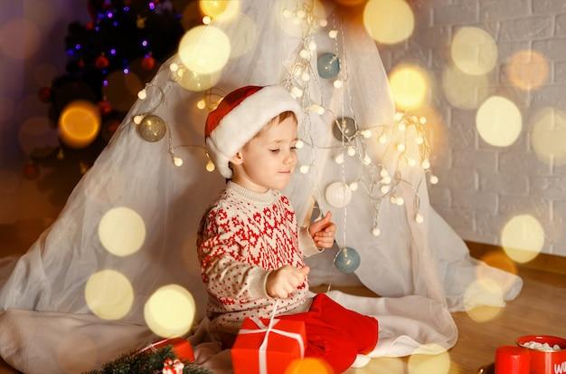 Criança adorável, aproveita o natal, férias em família, a criança desfaz os presentes