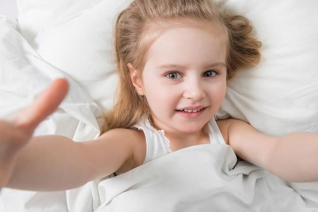 Criança adorável ativa acordada, lençóis brancos macios