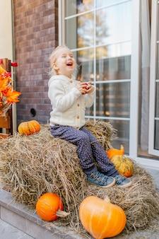 Criança adorável bebê loiro no casaco de malhas brancas, sentado no palheiro com abóboras na varanda, brincando com maçã e rindo