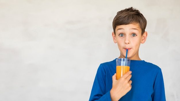 Criança adorável bebendo um pouco de suco de laranja