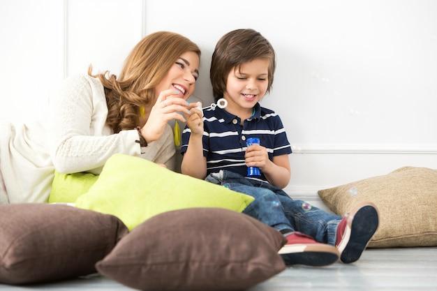 Criança adorável com a mãe fazendo bolhas