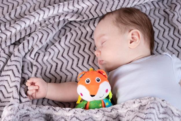 Criança adorável, com um brinquedo favorito, dorme relaxada e se esparrama na cama dos pais
