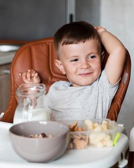 Criança adorável com uma variedade de lanches na mesa
