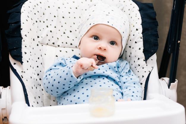 Criança adorável comendo com uma colher na cadeira alta