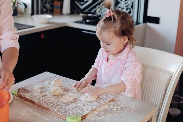 Criança adorável cozinhar com a mãe na cozinha